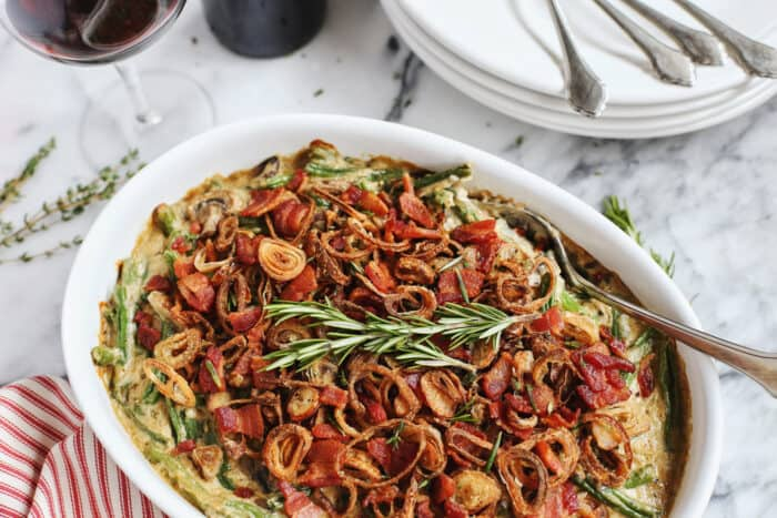 white serving dish with casserole of green beans, gravy, shallots, and bacon