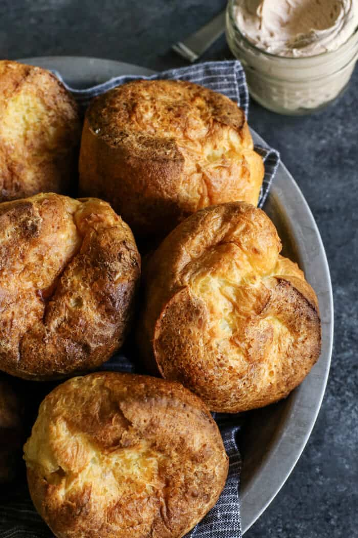 baked popovers in a metal plate, with a jar of cinnamon honey butter on the side