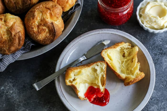 a popover split open on a plate, with butter and jam