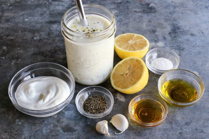a jar of lemon yogurt dressing, plus yogurt, cut lemon halves, garlic, olive oil, honey, salt and pepper