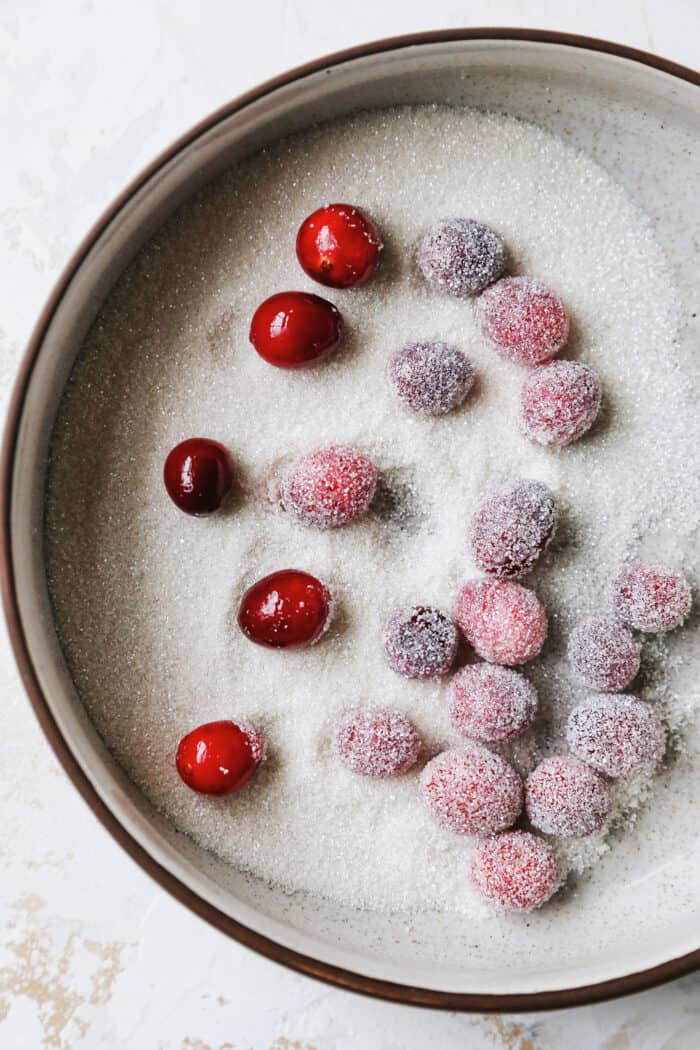 cranberries coated in simple syrup, rolled in sanding sugar in a small bowl