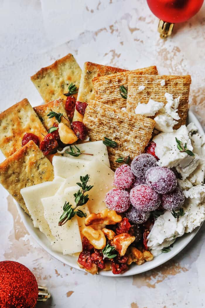 a plate of cheese, crackers, and nuts, plus candied cranberries