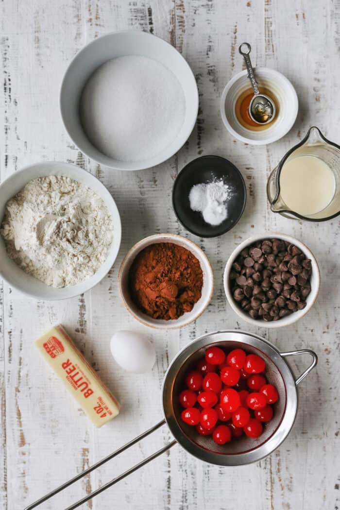 ingredients for chocolate cherry cookies laid out on a white table