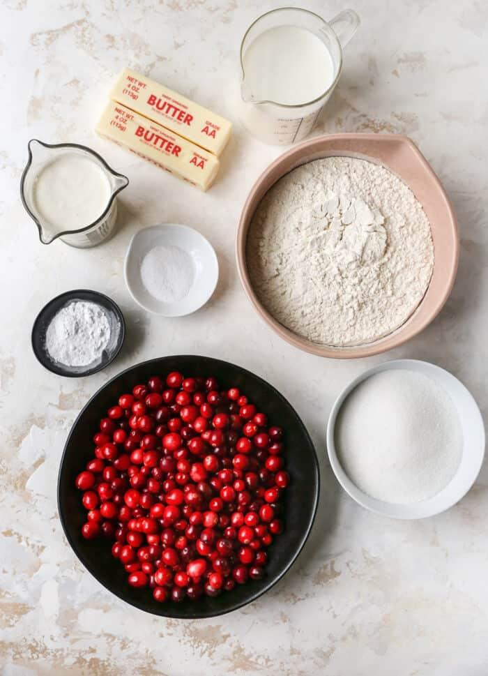 bowls of fresh cranberries, flour, sugar, baking powder, and salt, plus butter, milk, and heavy cream