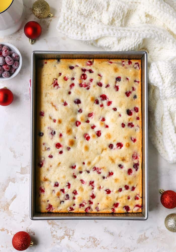 cranberry Christmas cake baked in a metal pan, with Christmas ornaments on the side