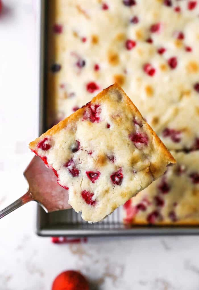 a spatula lifting a piece of Christmas cranberry cake out of the pan