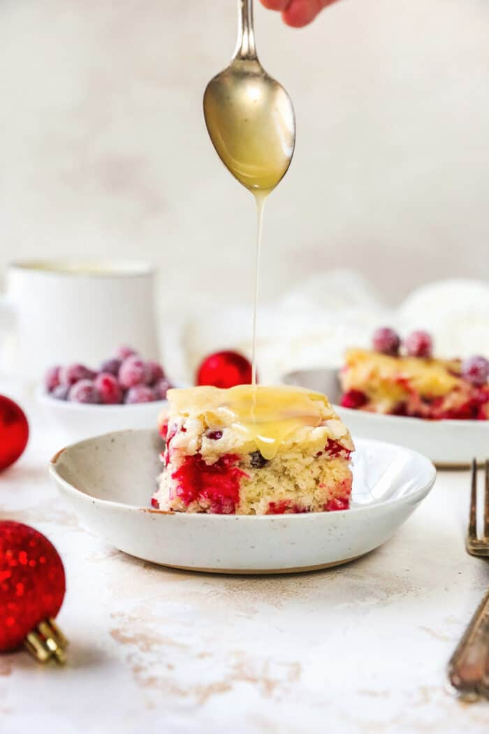 butter cream sauce being spooned over a piece of cranberry cake