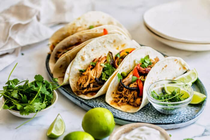a platter of tacos with carnitas meat and sauteed sweet peppers