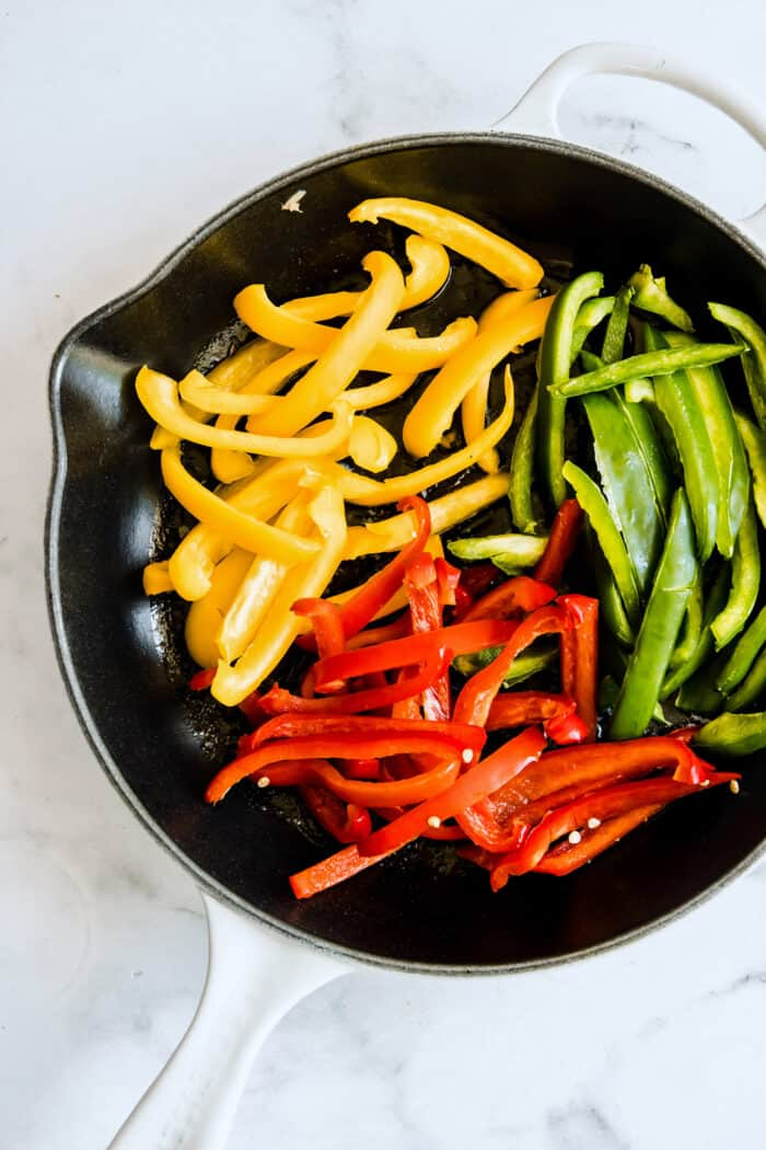 strips of raw colorful bell peppers in a white skillet