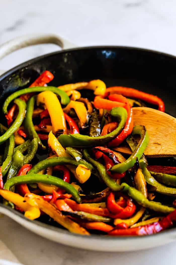 sauteed bell peppers in a white skillet
