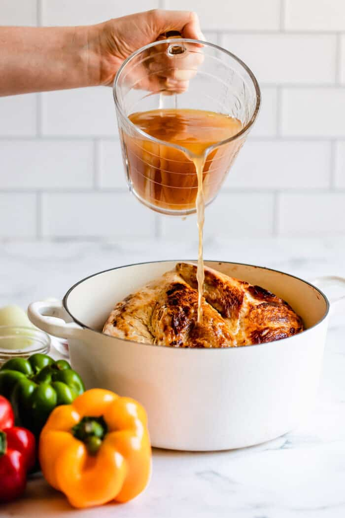 pouring chicken broth into pot with seared pork shoulder