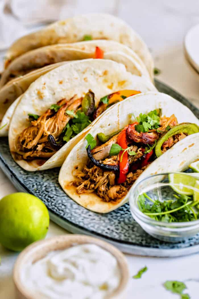 a platter of carnitas tacos with sauteed sweet peppers