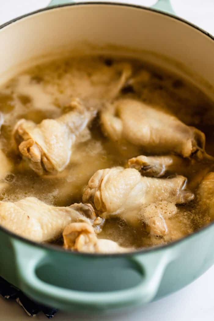 a large pot of water with chicken wings parboiling in it