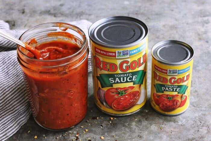 jar of homemade pizza sauce and a can of tomato sauce and tomato paste