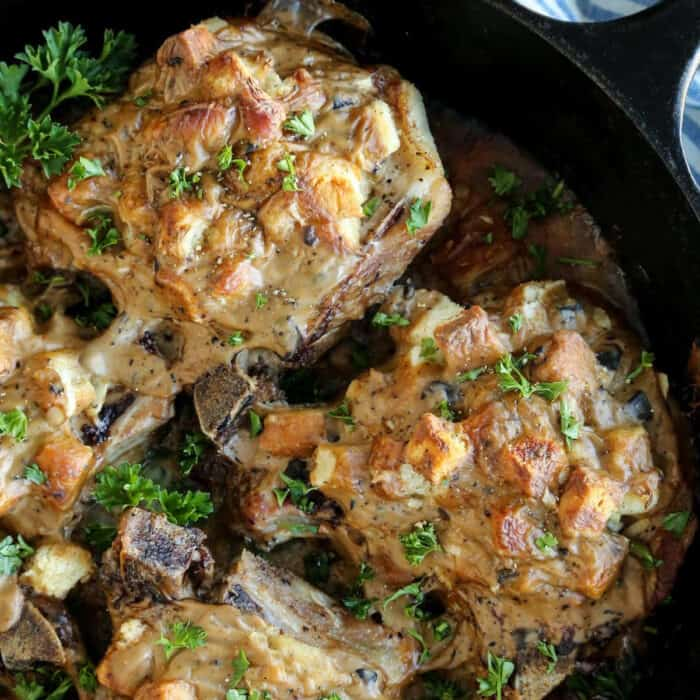 baked pork chops covered in stuffing, in a cast iron skillet