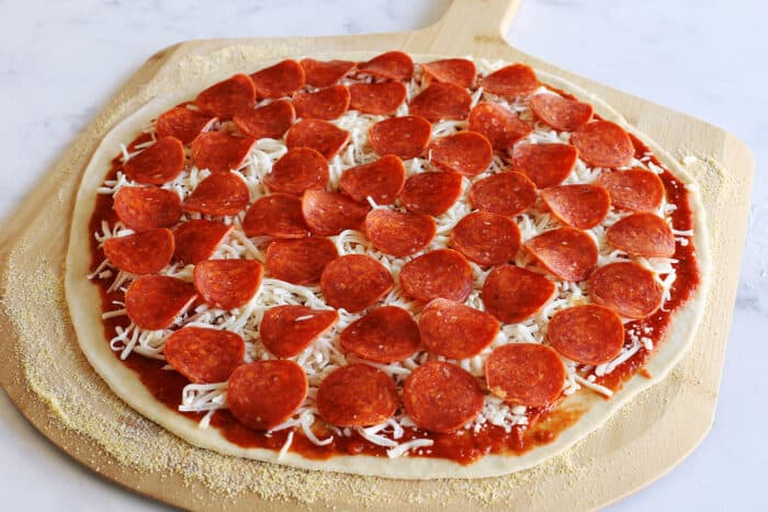 pepperoni on top of the cheese on the pizza