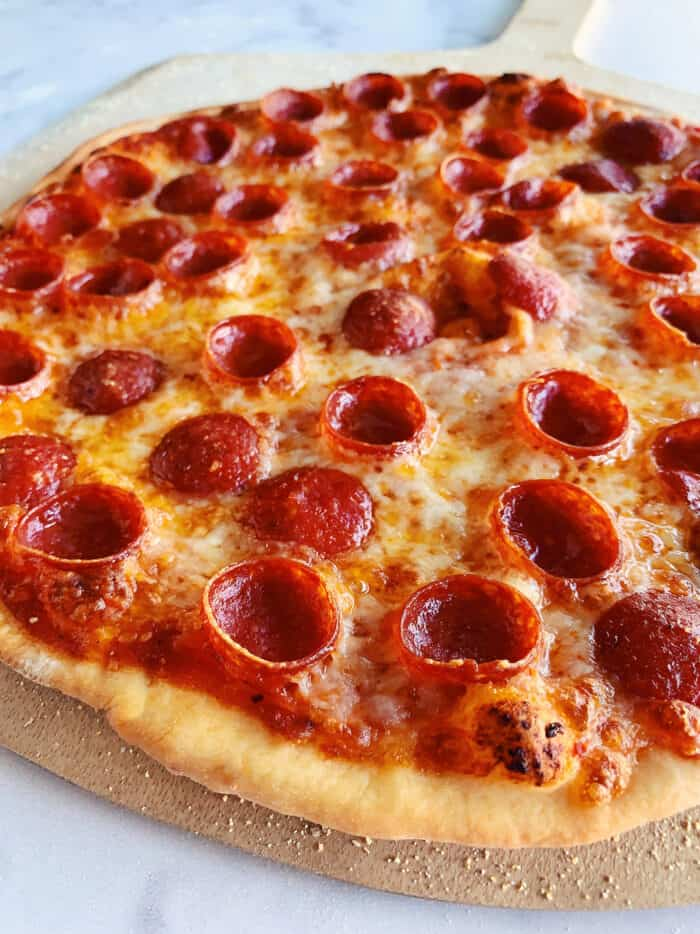 a baked pepperoni pizza on a wood pizza peel