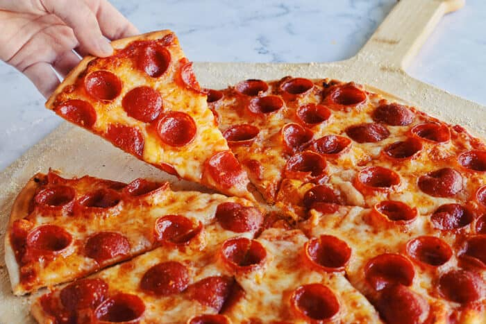 a hand taking a slice of pepperoni pizza