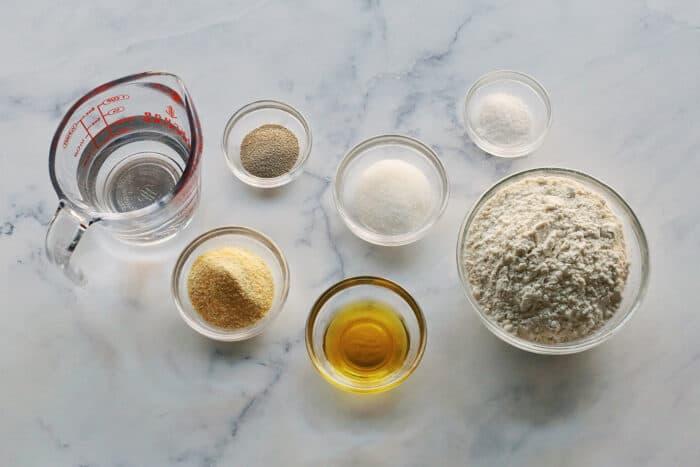 ingredients to make thin crust pizza dough: flour, yeast, olive oil, salt, sugar, water