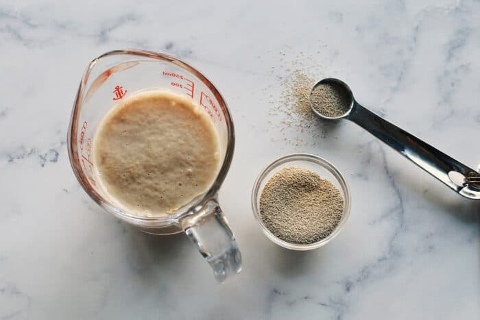 a small bowl of yeast, plus yeast foaming in a clear measuring cup of water