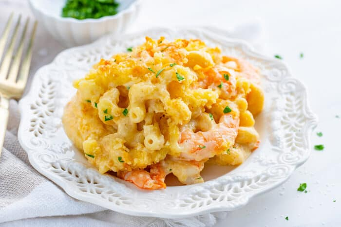 a serving of baked macaroni and cheese with shrimp on a white plate