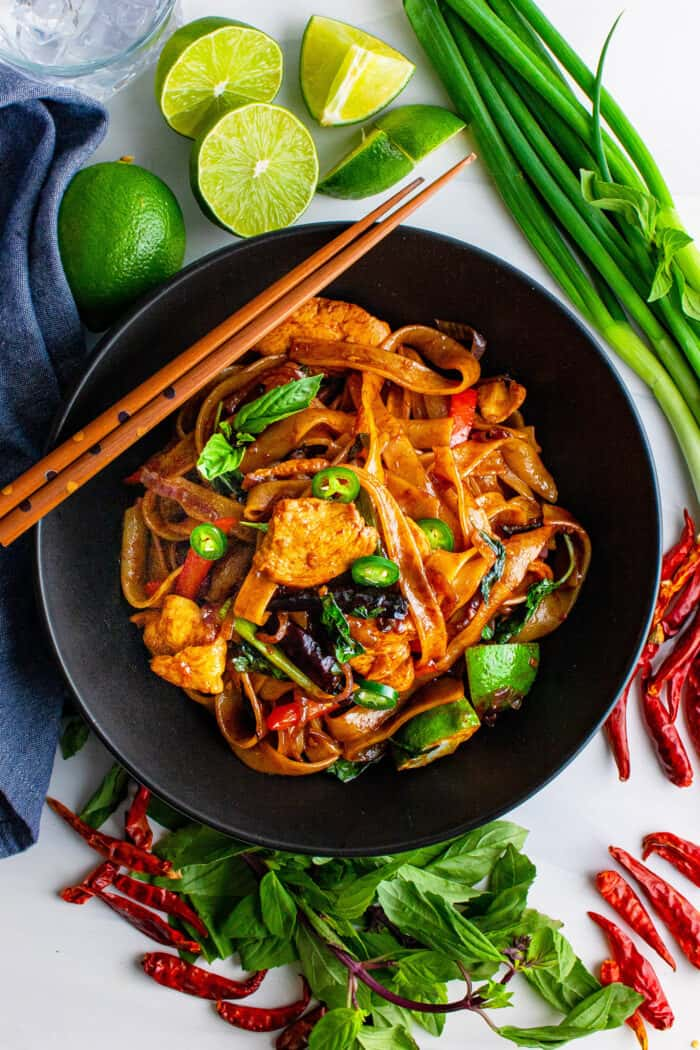 a black bowl of drunken noodles, with fresh ingredients on the table