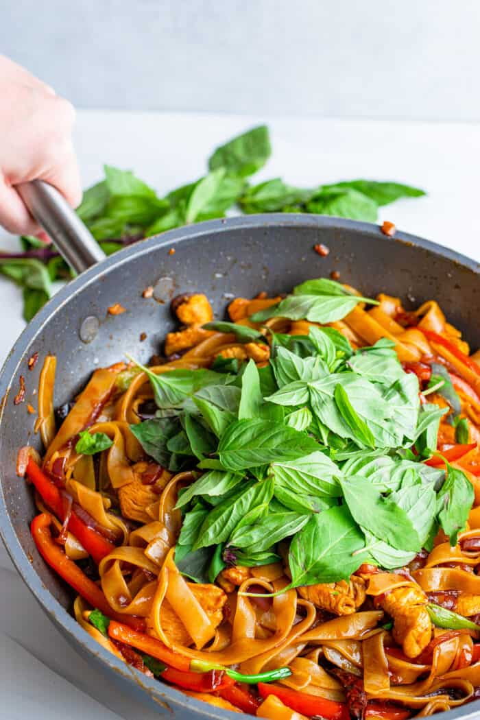 a pan of Thai drunken noodles topped with fresh Thai basil leaves