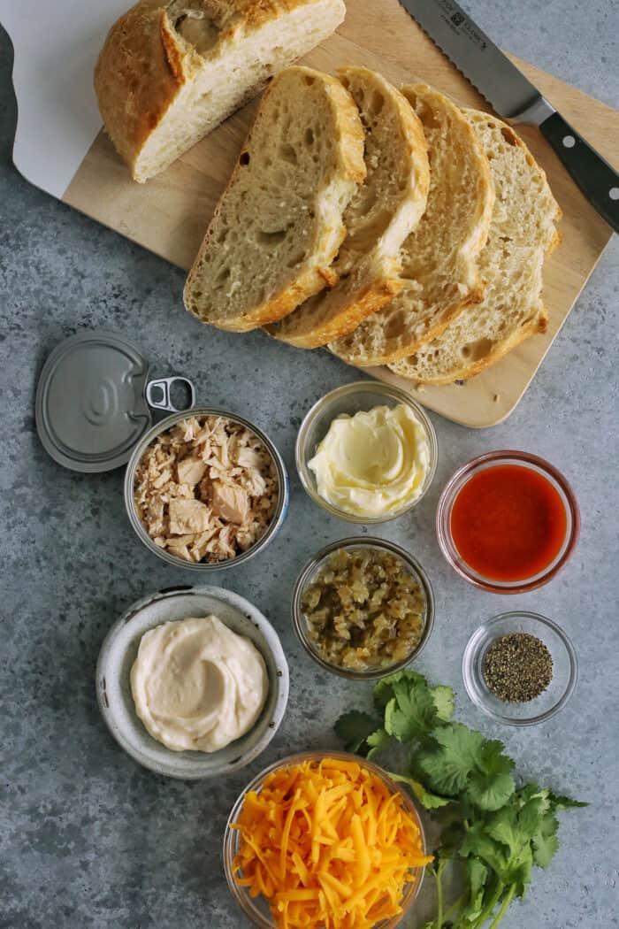 ingredients for a tuna melt - tuna, bread, butter, mayo, pickle relish, cheese, sriracha, cilantro, black pepper