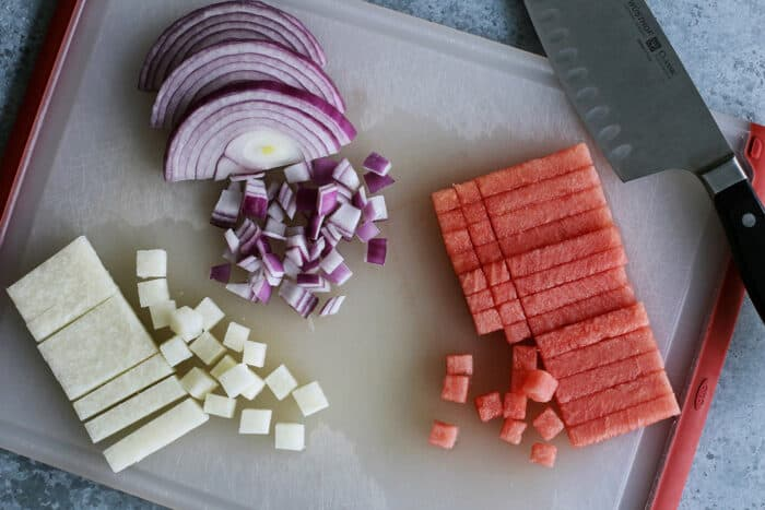 dicing watermelon, jicama, and red onion on a cutting board
