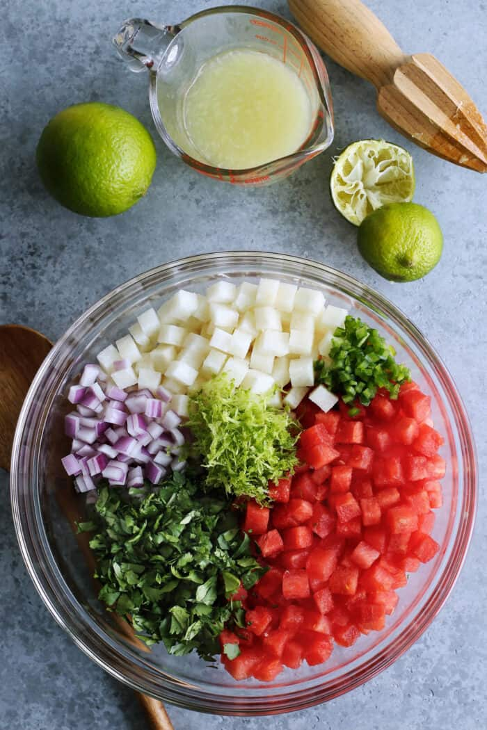 prepared ingredients for watermelon salsa in a clear bowl plus freshly squeezed lime juice