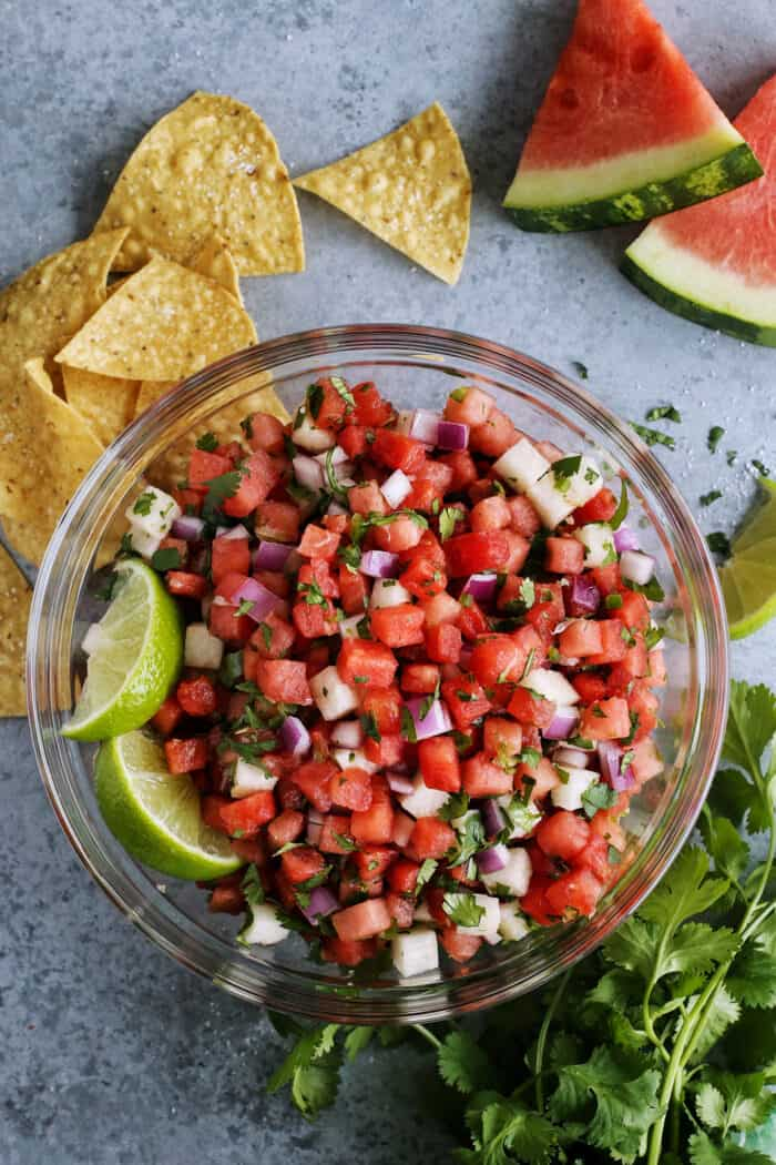 watermelon salsa in a clear bowl with tortilla chips and wedges of fresh watermelon