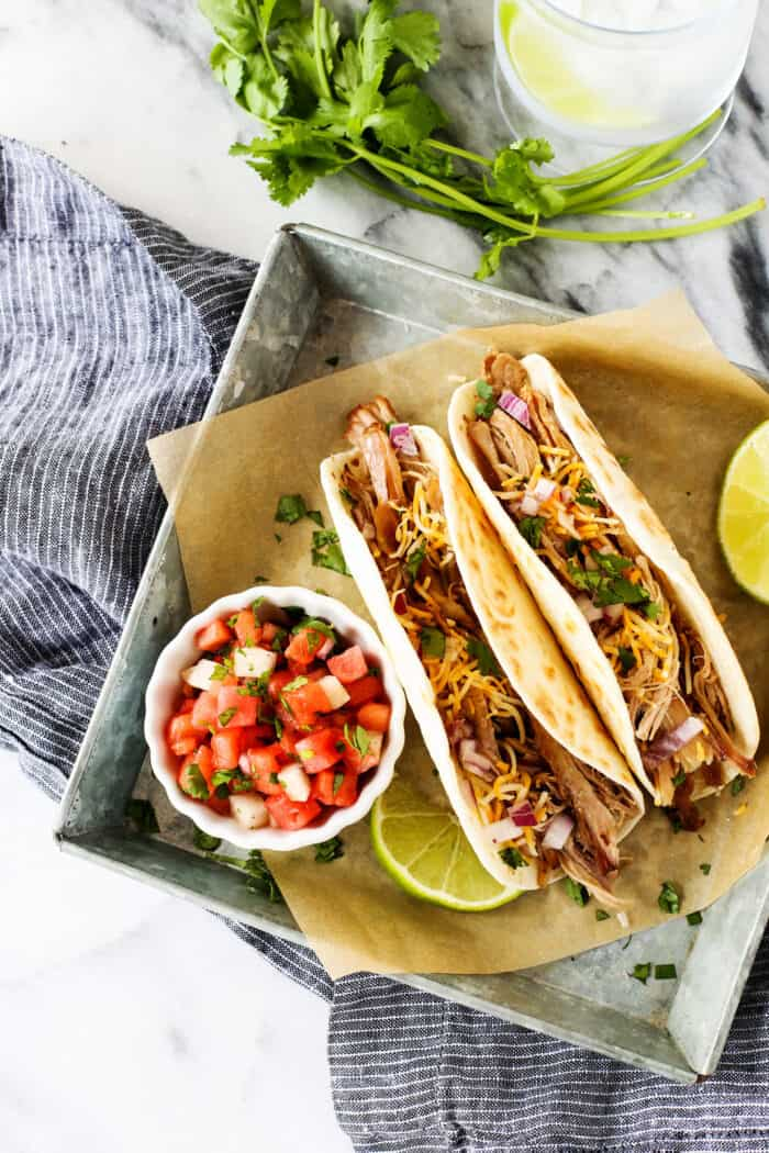 carnitas tacos with a cup of watermelon salsa