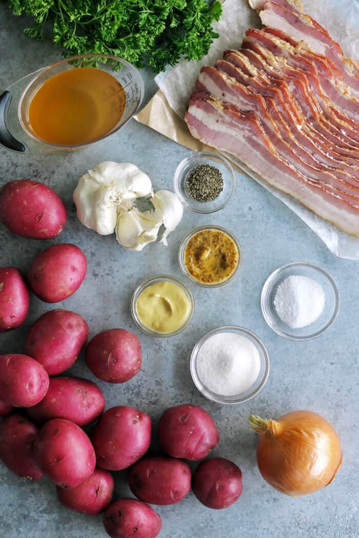 ingredients for potato salad: red potatoes, onion, garlic, bacon, apple cider vinegar, whole grain and Dijon mustards, sugar, salt and pepper