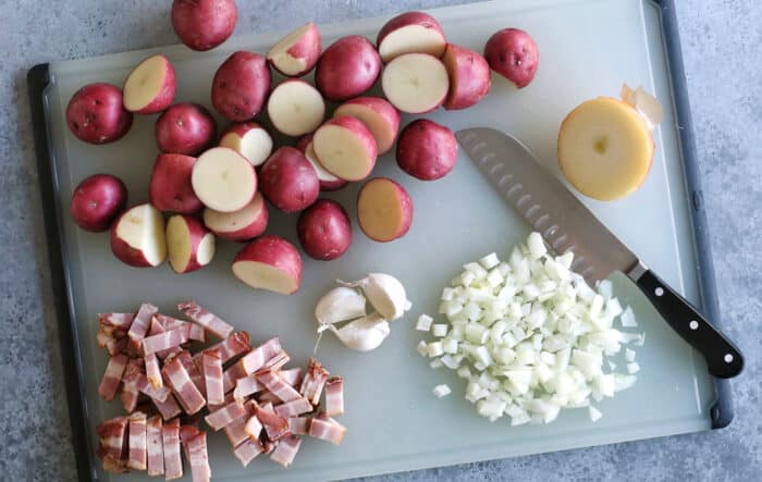 potatoes, onion, garlic, and bacon on a cutting board with a chef's knife