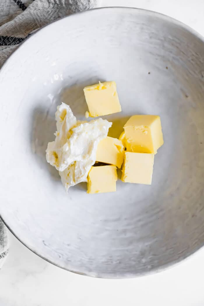 cream cheese and chunks of butter in a wide white bowl