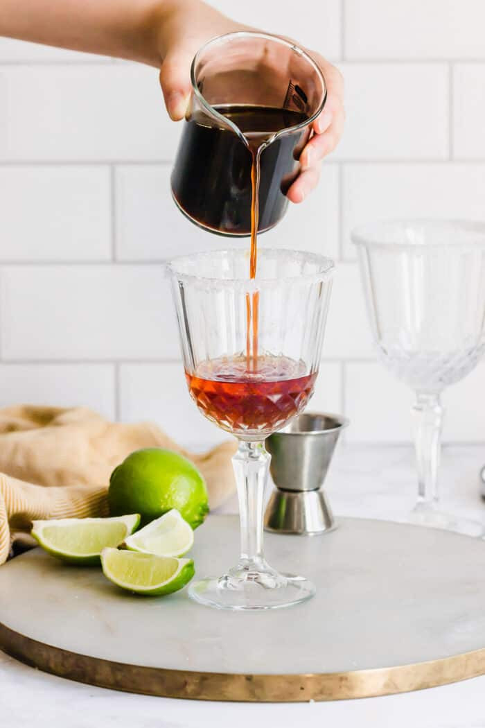 pouring coffee into a stemmed glass with liqueurs