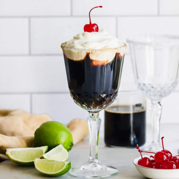 Mexican coffee cocktail in a stemmed glass, plus fresh limes and stemmed maraschino cherries