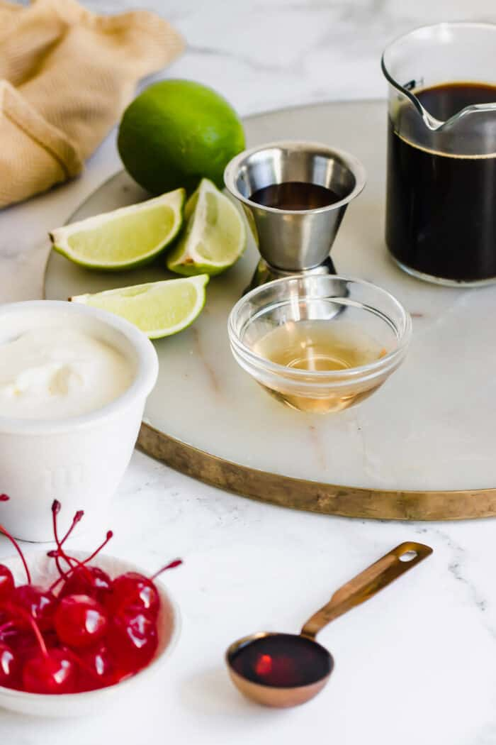 ingredients to make a Mexican cocktail with coffee, liqueurs, whipped cream, and cherries