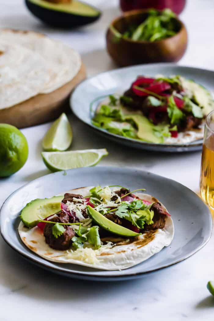 mole pork tacos on plates, plus fresh limes, tortillas, and a glass of beer