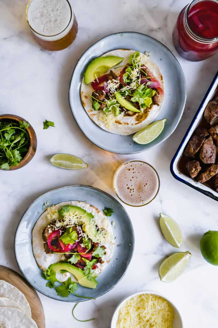 plates of tacos with pork mole, glasses of beer, a jar of pickled red onions, a pan of cooked pork