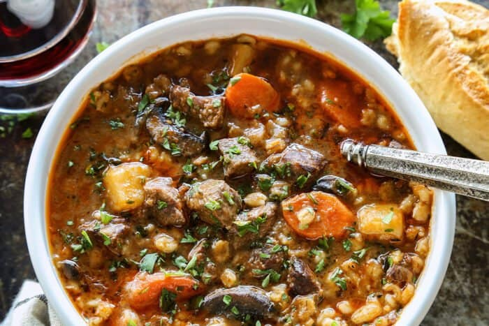 beef barley soup in a white bowl, plus crusty bread and glass of red wine