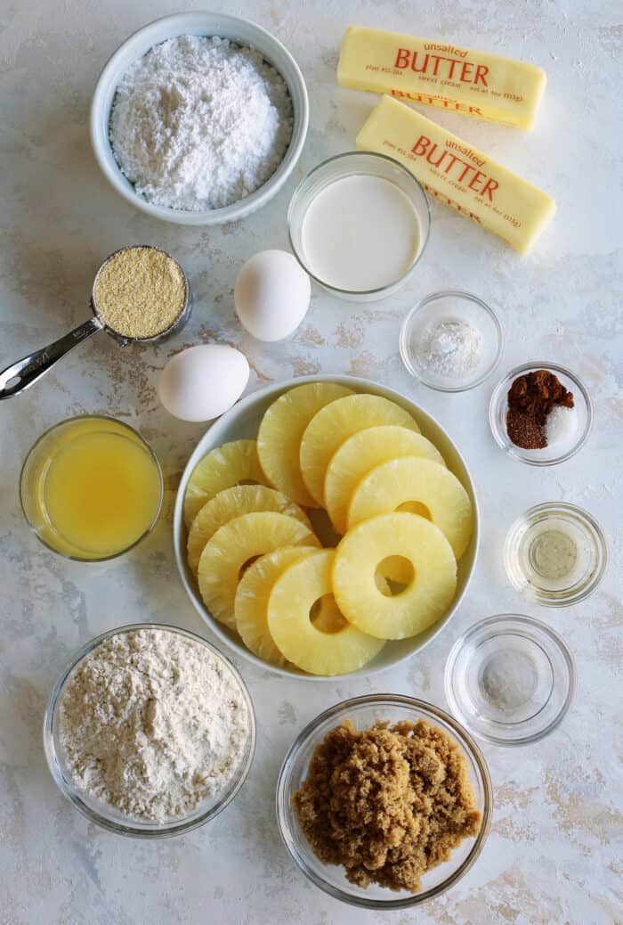 ingredients to make cake, to include pineapple rings and juice, flour, cornmeal, powdered sugar, brown sugar, eggs, and butter