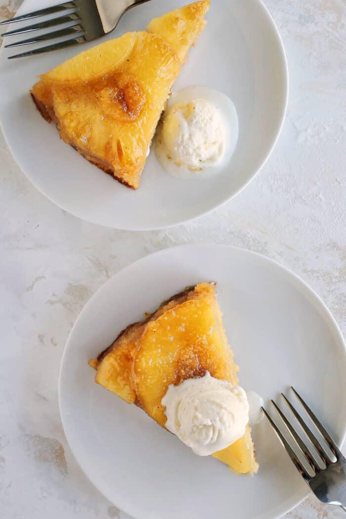 slices of pineapple cake with scoops of vanilla ice cream on white dessert plates