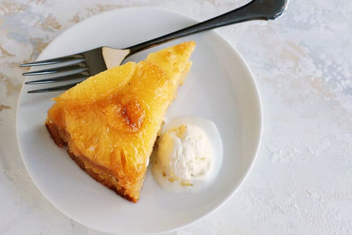 a slice of pineapple cake with a scoop of ice cream on a white plate