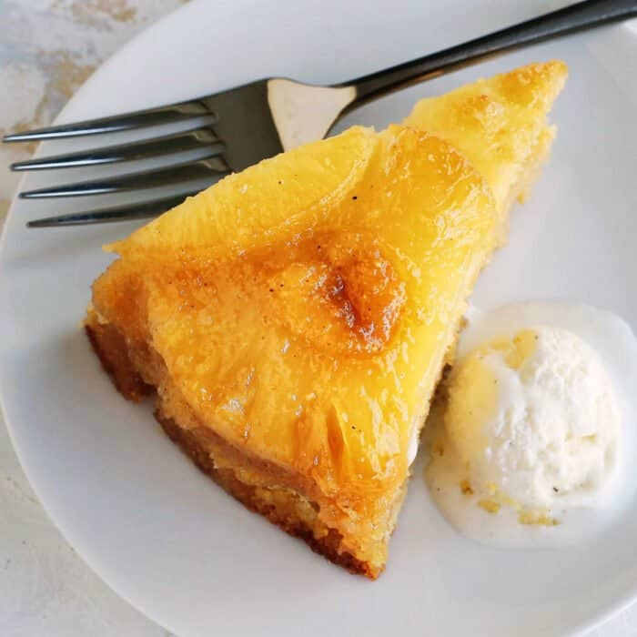 a close-up photo of a slice of pineapple cake with ice cream