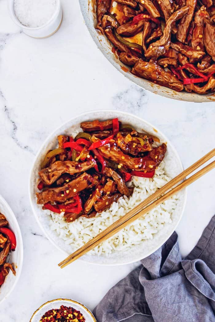 a serving of Beijing beef over white rice in a white bowl, with wood chopsticks
