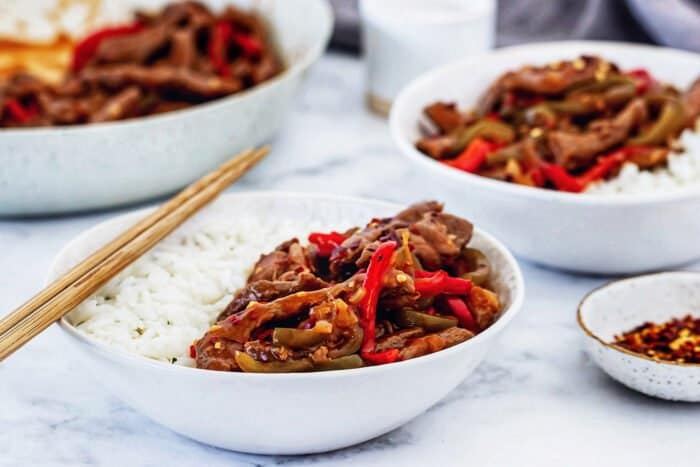 individual bowls of rice, beef, and vegetables with a skillet in the background
