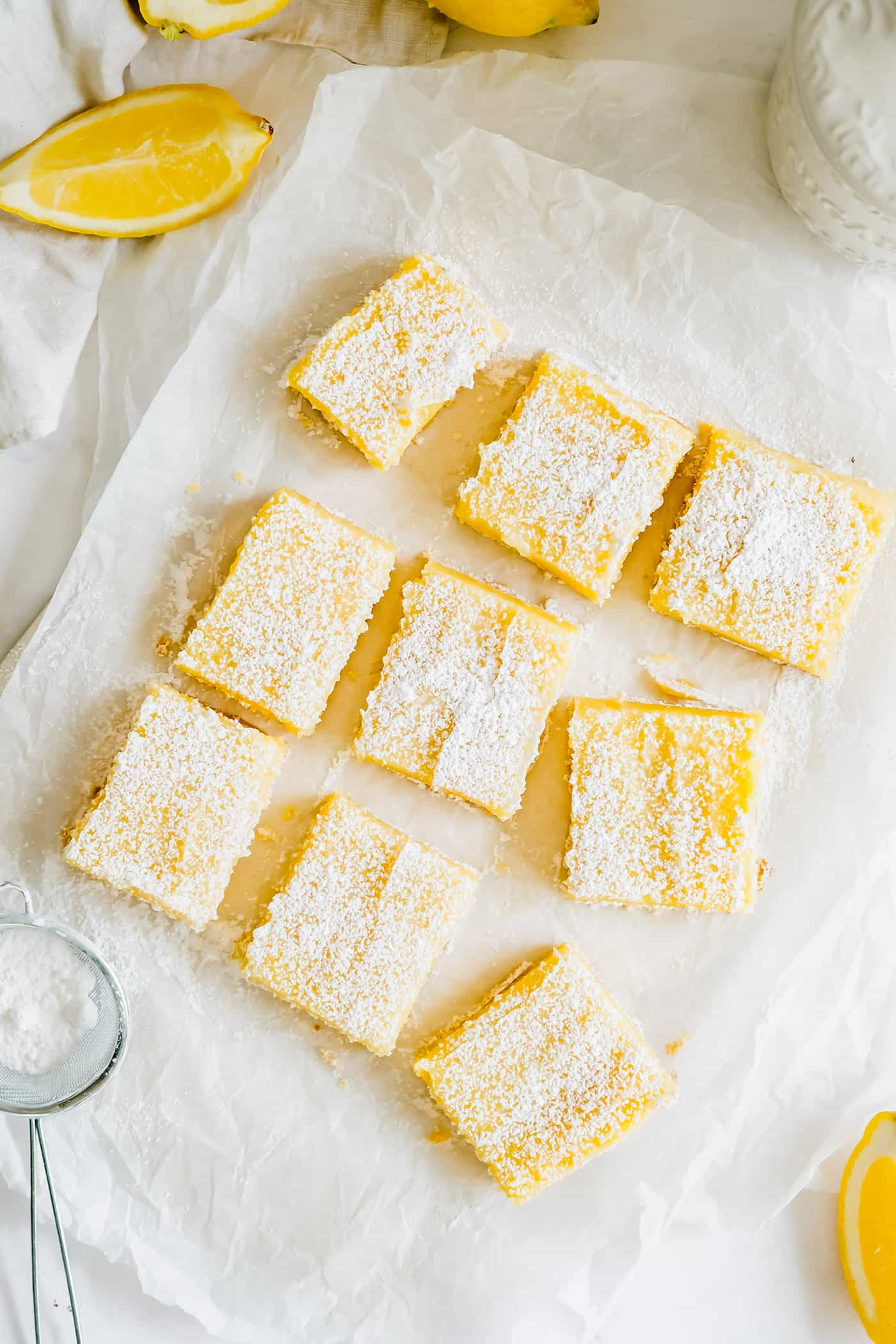 Lemon bars cut and sprinkled with powdered sugar, on a piece of white parchment paper