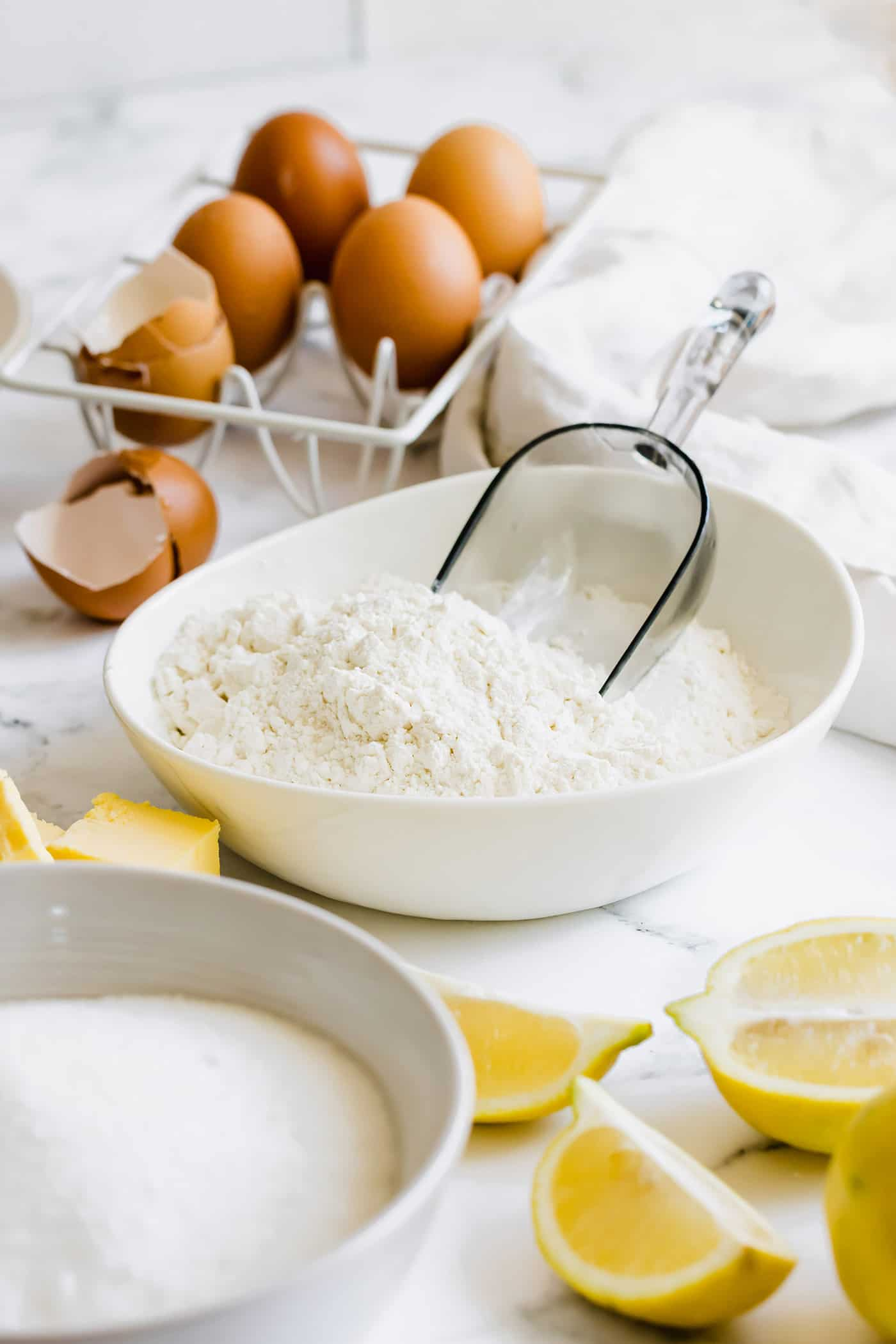 bowls of flour and sugar, plus fresh lemons, cubes of butter, and eggs