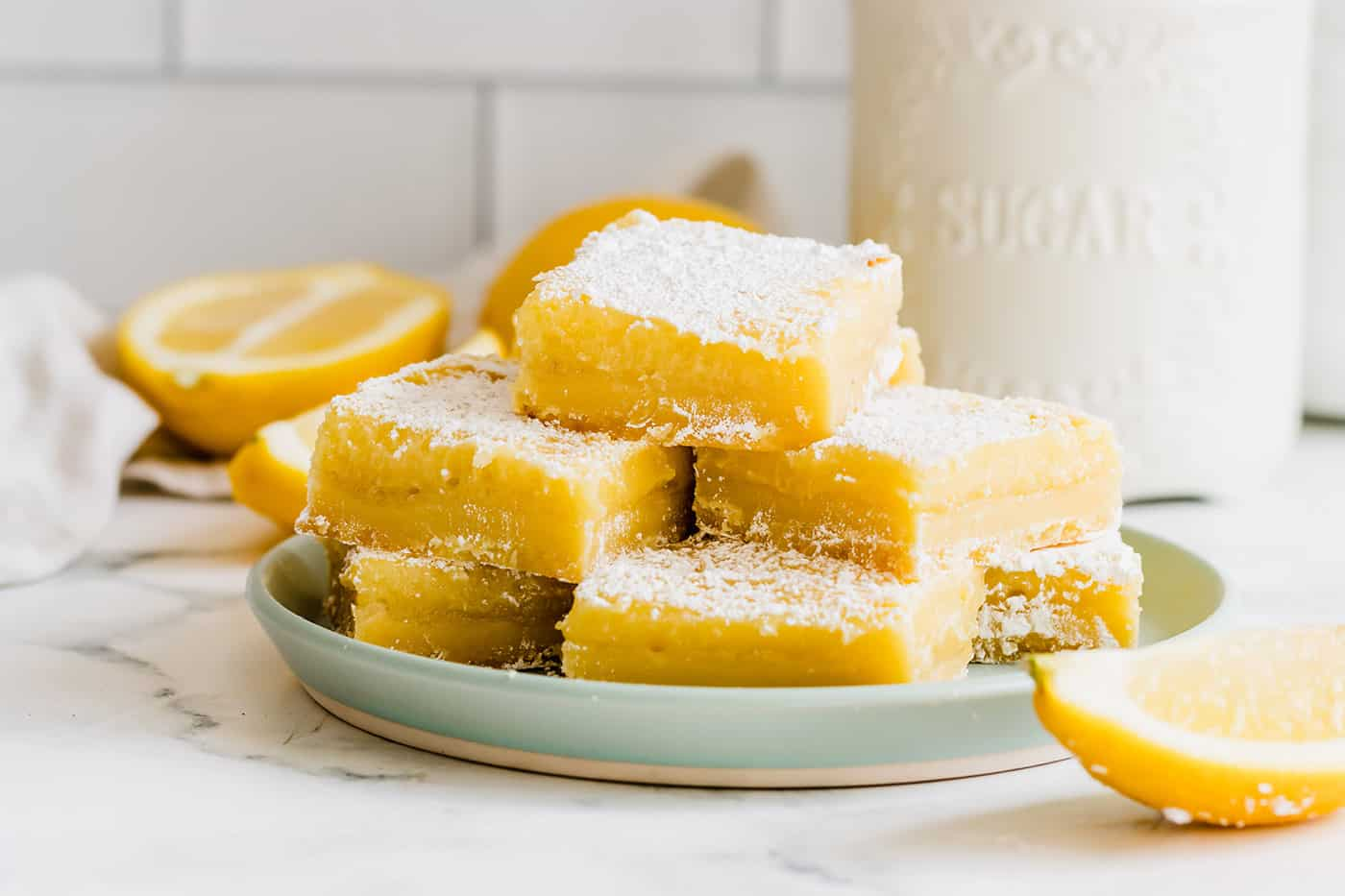 a light green plate with a stack of bars consisting of a shortbread crust and lemon curd filling